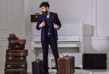 Baggage and travelling concept. Macho stylish on thoughtful face standing near pile of vintage suitcase. Man, traveller with beard and mustache with luggage, luxury white interior background.