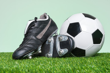 Football or Soccer boots and ball on grass