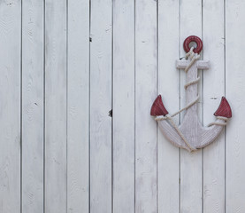 decorative wooden anchor on a white wooden wall