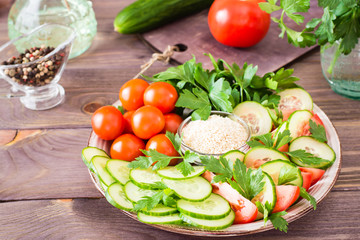 Fresh slices of cucumbers, tomatoes, sesame seeds in a bowl and parsley leaves on a plate on a wooden table. Oil and seasoning for cooking vegetable salad