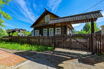 Traditional Russian old country wooden house with fence.