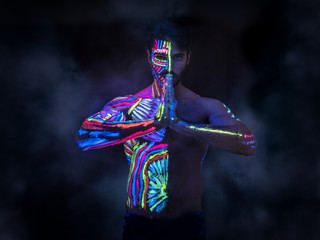 Young man painted in fluorescent paint on face and muscular torso, in studio shot with UV light