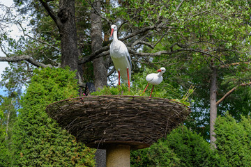 White artificial storks as a part of a landscape design.
