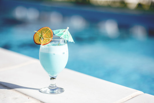 Close-up of summer cocktail on the beautiful blue water background during the sunlight