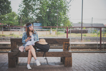 Asian tourist wait train at train station,thailand hipster man go to travel