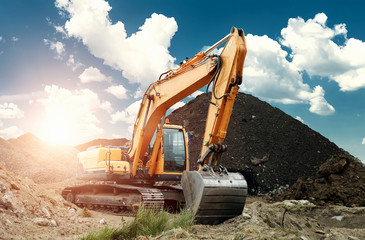 Excavator at the construction site, sand, crushed stone, against the blue sky background. Construction equipment, construction.