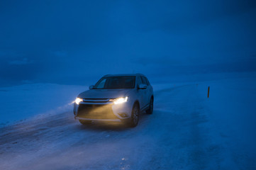 SUV driving on snowy icy road in Northern Iceland at night