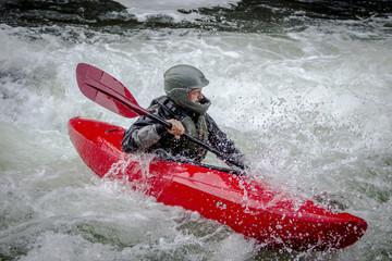 Whitewater kayaker paddling through turbulent river