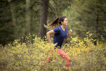 Woman trail running in forest