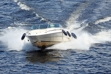 white motor boat flying fast on the waves