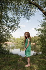 Serious girl standing by lake
