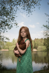 Girl holding chicken by lake