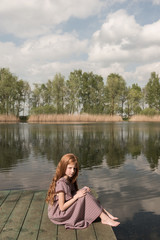 Serious girl sitting on dock