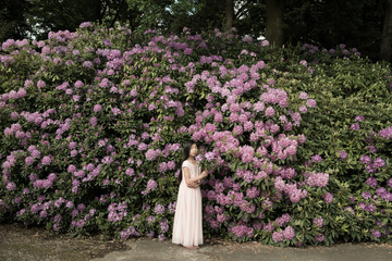 Girl standing in front of purple rhododendron