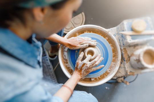 smiling woman making ceramic dishware on pottery wheel with clay, workshop and leisure concept