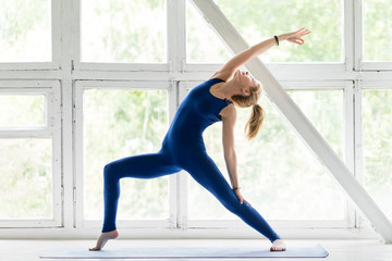 Portrait of attractive sporty young woman practicing yoga indoor near retro windows. Beautiful fitness girl doing yoga asana in class. Healthy lifestyle, calmness and relax