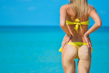 Sexy sandy woman buttocks on tropical beach background near ocean. close up outdoor shot of young woman in yellow bikini, sunbathing at sea shore. Yellow bikini on ocean background