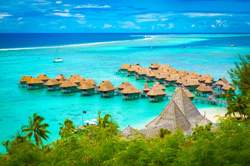 Aerial view of overwater bungalow luxury resort in turquoise lagoon water of Moorea, French Polynesia.
