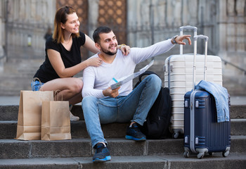 Attractive man and woman sitting at stairs with map
