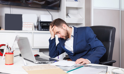 Frustrated sales manager working on laptop