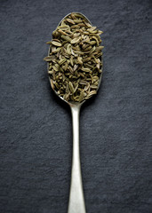 Fennel seeds on vintage teaspoon. Slate background