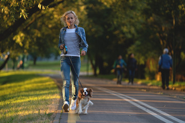 Beautiful young woman playing with her Dog in the Park in the autumn