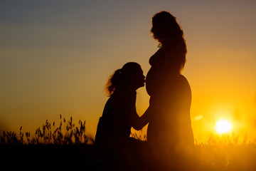 Young couple at sunset, the husband kisses the pregnant wife in the belly against the background of a romantic sunset in the grass.