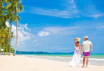 young couple on their honeymoon having fun by tropical beach