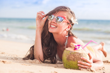 beautiful longhaired woman in sunglasses drinking coconut cocktail by the beach