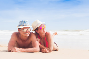 happy young couple lying and having fun on a tropical beach