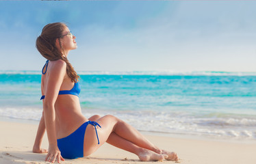 young longhaired woman in sunglasses and bikini smiling and sunbathing by the beach