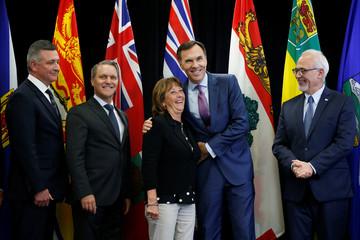 Canada's Finance Minister Bill Morneau embraces Nova Scotia's Finance Minister Karen Casey while posing for a group photo in Ottawa