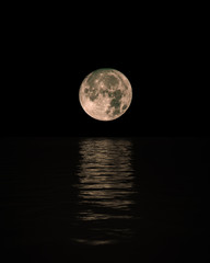 Full Moon Rising Over Calm Sea with reflection on water, Vertical