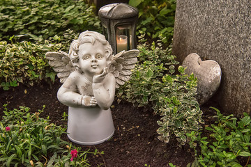 Munich, Germany - June 09, 2018: Little angel figurine and heart on the grave