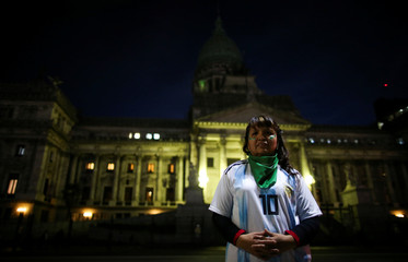 A woman wearing an Argentine national soccer shirt poses for a picture during a protest in favour of legalising abortion outside the National Congress in Buenos Aires