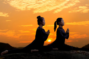 The silhouette of two young girls practicing yoga on the stone at sunset time sky background.