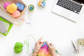 The girl knits the colored canvas with knitting needles. Laptop, basket with skeins of yarn, coffee, tea and water with lemon.