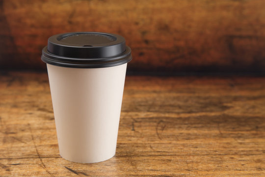 Disposable White Paper Coffee Cup with a Black Lid on a Wooden Counter