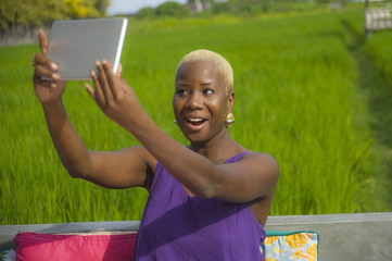 young attractive and happy black afro american woman outdoors taking selfie with digital tablet pad on green grass field background enjoying Summer