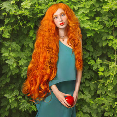 Young redhead princess with very long hair in blue dress on a green summer background. A beautiful woman with pale skin, red lips and blue eyes. Princess with red apple in the garden