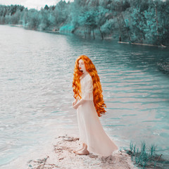 Young unusual woman with long hair, red lips, pale skin on blue water background. Beautiful redhead model against the lake. Unusual summer landscape