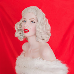 Beautiful blonde woman with birthmark on face in white fur coat on red background. Portrait of young pale girl with white hair. Beautiful woman with birthmark on her cheek and earrings on ears