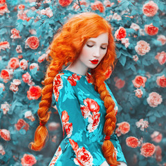 Young beautiful redhead girl with very long hair braided in plait on rose background. Fabulous renaissance woman in a flower dress against the backdrop of a beautiful rose bush. Doll with plait