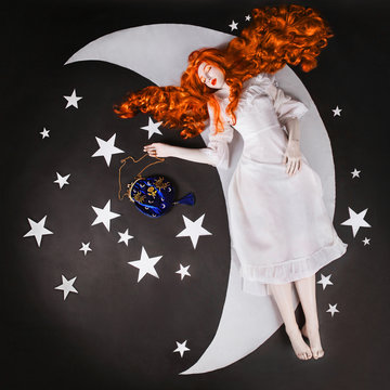 The moon and the stars. Young fairy woman with very long hair in white dress on black background. A beautiful girl with pale skin. Renaissance fairy princess sleep on the moon. Sweet dream