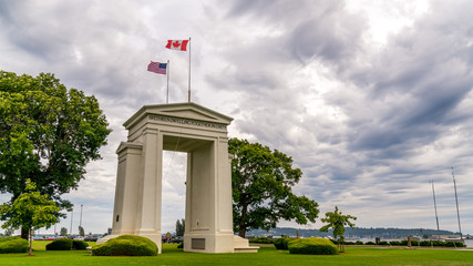 Vancouver-Blaine Hwy, Surrey, British Columbia, Canada - US Peace Arch border crossing. Canadian and US flags are waiving in the wind on a beautiful cloudy sky.