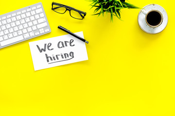 Search for worker, employee concept. We are hiring lettering on work desk on yellow background top view copy space