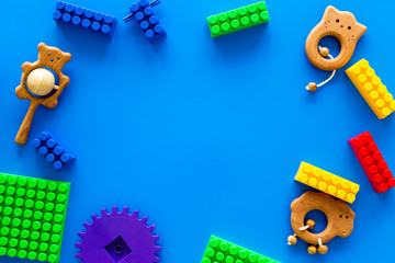 Colored construction toys for children frame on blue background top view copy space