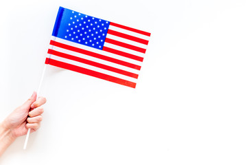 American flag concept. Hand hold small flag on white background top view copy space