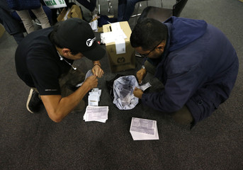 Electoral officials rip up ballots after tables closed during the second round of the presidential election in Bogota