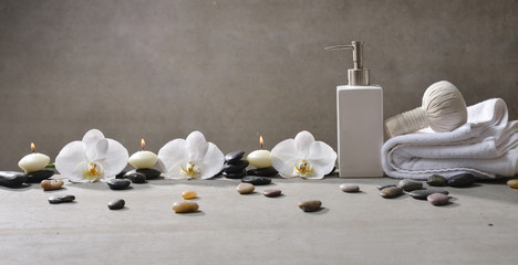 Three candle with pile of stones and white orchid , herbal ball.on towel ,oil on gray background